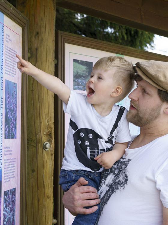 Vater und Sohn erkunden Wandertafel